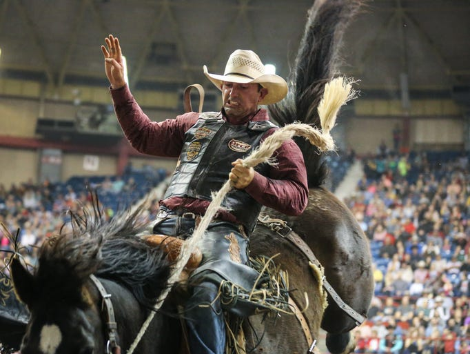 Nick LaDuke rides a bronc during the 9th performance