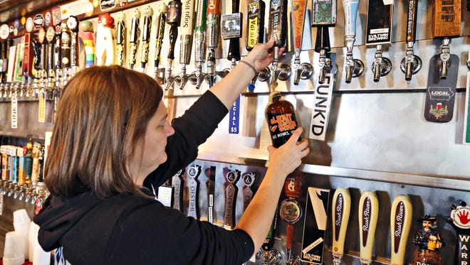 Bartender Teresa Ceretti pours a growler of Stone coffee milk stout at El Bait Shop Friday, Nov. 7, 2014