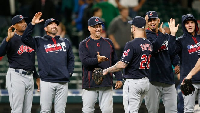 Cleveland Indians manager Terry Francona (center) slaps hands with first baseman Mike Napoli (26) after a game against the Seattle Mariners at Safeco Field. Cleveland won 5-3.