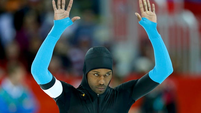 Shani Davis of the U.S. waves before competing in the men's 1,500 meter speedskating race during the 2014 Sochi Winter Olympics, Feb. 15, 2014. U.S. speed-skaters decided on Friday to drop new, specially designed Under Armour suits.