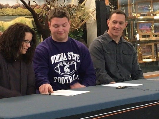 Marshfield senior Quinton Alexander smiles after signing his letter of intent with the Winona State University football team during a ceremony Wednesday at Marshfield High School.