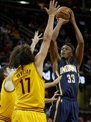 Indiana Pacers' Myles Turner, right, shoots over Cleveland Cavaliers' Joe Harris, left, and Anderson Varejao, in an NBA preseason game, Thursday, Oct. 15, 2015, in Cleveland.