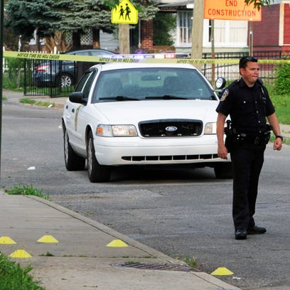 An officer stands next to a grouping of evidence markers