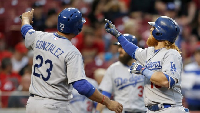 Los Angeles Dodgers first baseman Adrian Gonzalez (23) and Los Angeles Dodgers third baseman Justin Turner (10), right, celebrate Turner's home run by pretending to take a picture in the third inning during the MLB game between the Cincinnati Reds and the Los Angeles Dodgers, Tuesday, Aug. 25, 2015, at Great American Ball park in Cincinnati, Ohio.