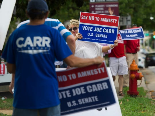 Opponents of Sen. Lamar Alexander, including Kelly Turberville of Clarksville, picket across the street from a rally of Lamar supporters in front of his campaign headquarters.