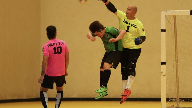 Papi FC goalkeeper David Drews leaps to punch the ball away from Bank of Guam Strykers' Scott Spindel in a semifinal match of the Budweiser Futsal League played Wednesday evening at the Guam Sports Complex gym. Papi FC won 8-5.