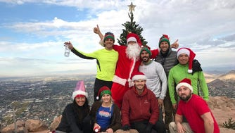 A group carried a new Christmas tree to the top of Camelback Mountain on Friday, Dec. 2, in Phoenix.
