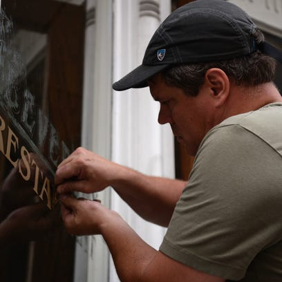 Chip Clarke scrapes away the lettering of the Beverley