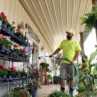 Brandon Warfield waters plants on the front porch of