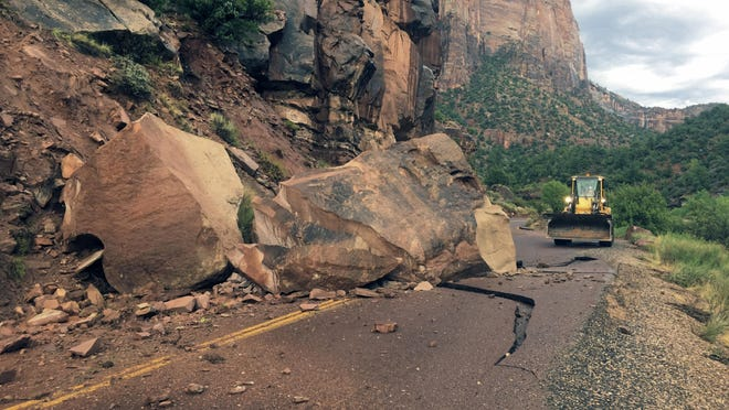 This Wednesday, Aug. 10, 2016 photo provided by the National Park Service shows the Zion-Mount Carmel Highway, State Route 9 closed, in Zion National Park after a boulder tumbled onto the roadway. Park spokeswoman Aly Baltrus says a geologist is exploring the best way to get the massive rock off the Zion-Mount Carmel Highway, where it fell on Wednesday evening.