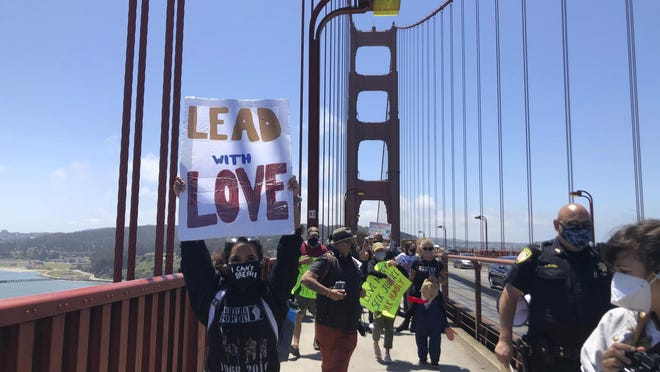 Dozens of people march across the famous Golden Gate Bridge on Saturday in support of the Black Lives Matter movement.