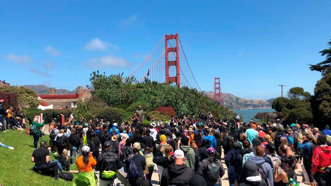 Dozens of people gather by the Golden Gate Bridge Welcome Center in San Francisco Saturday, June 6, 2020, to begin marching across the famous span in support of the Black Lives Matter movement.