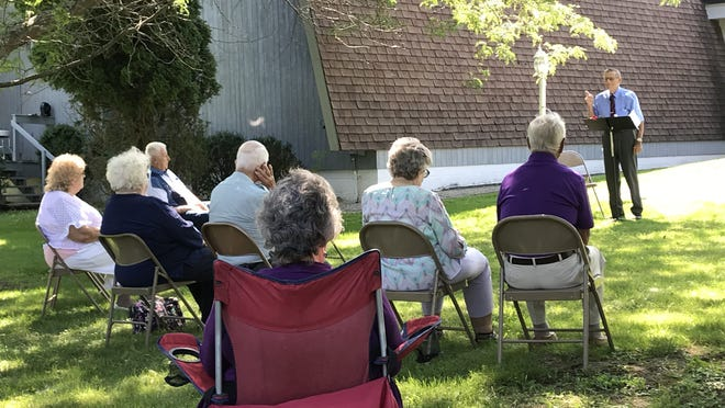 Pastor John Karle gives his message to the Faith Bible Church congregation gathered on the front lawn of the Honeoye church on Sunday, Aug. 9.