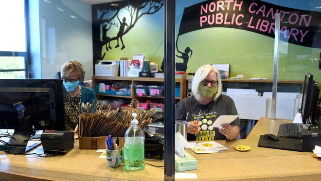 Library Associates Edyta Metz (left) and Carolyn McBee work in The North Canton Library Children's Department as they prepare to welcome back children on Tuesday
