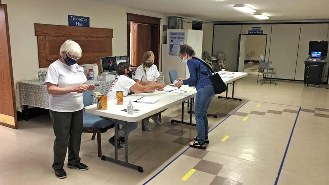 A voter provides identification June 2, 2020 for the municipal election at the Boonville Ward 2 voting location at Nelson Memorial United Methodist Church. Turnout at this location was fairly low.