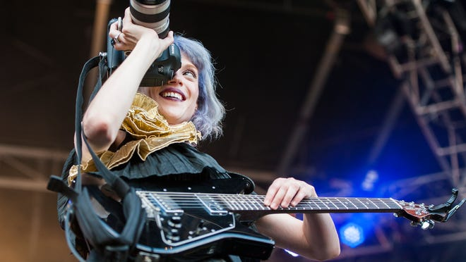 St. Vincent looks through a camera she took from pit photographer Erik Voake, not pictured, during her performance at the Austin City Limits Music Festival in 2014.