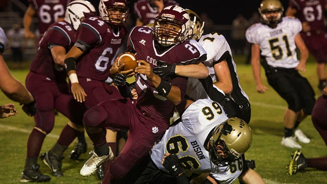 Stuarts Draft's Marston Jones is brought down by Buffalo Gap's Tristan Anderson, top, and Caleb Smiley, bottom during their football game Friday at Stuarts Draft High School.
