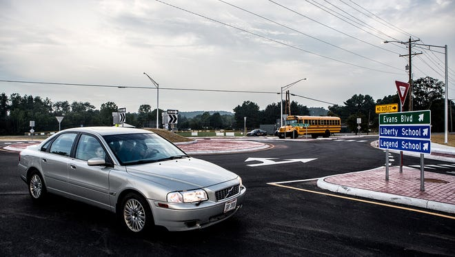 Buses and cars make their way around the new roundabout outside the entrance to Liberty Middle School and Legend Elementary school. The roundabout opened just in time for the first day of school and will hopefully make it safer for parents and bus drivers turning in and out of the access road onto Sharon Valley Road.