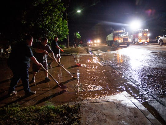 Washington City residents remove mud and water from