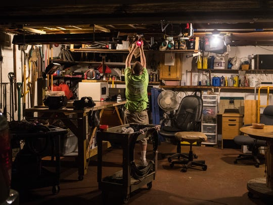 Bob Colegrove checks the color of a lightbulb in his workshop at his home in Wilmington.