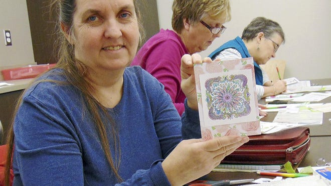 Paula Bushby of Effingham, Ill., shows off the 3-D card she created in an adult coloring class at the local public library.