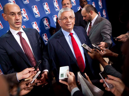 FILE - In this Nov. 10, 2011, file photo, NBA Commissioner David Stern, center, speaks to the news media alongside Deputy commissioner Adam Silver after a marathon meeting with the Players Association in New York. Former NBA Commissioner David Stern believes medicinal marijuana use should be allowed, but the league says it won't allow players to use it for recreational use. Adam Silver, who replaced Stern as commissioner in 2014, has said he is interested in studying more about the safety of medicinal marijuana.  (AP Photo/John Minchillo, File)