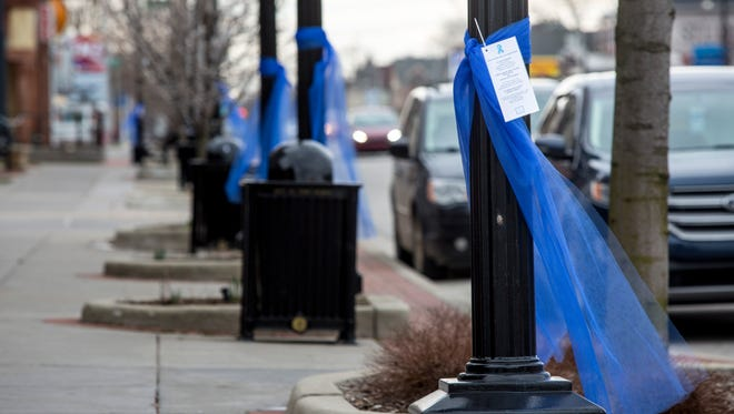 Blue ribbons hang on utility poles to bring awareness to child abuse prevention.
