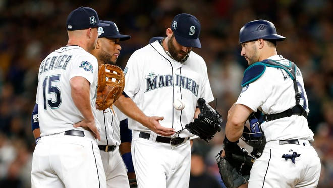 Seattle Mariners relief pitcher Tony Zych (middle) has a mound conference with catcher Mike Zunino (3), third baseman Kyle Seager (15) and second baseman Robinson Cano (22) during the eighth inning of Saturday's game against the Angels.