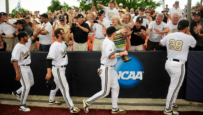 Vanderbilt pitchers celebrate a 4-2 win over Illinois with fans at the NCAA Super Regional at Illinois Field on June 8, 2015, in Champaign, Ill.