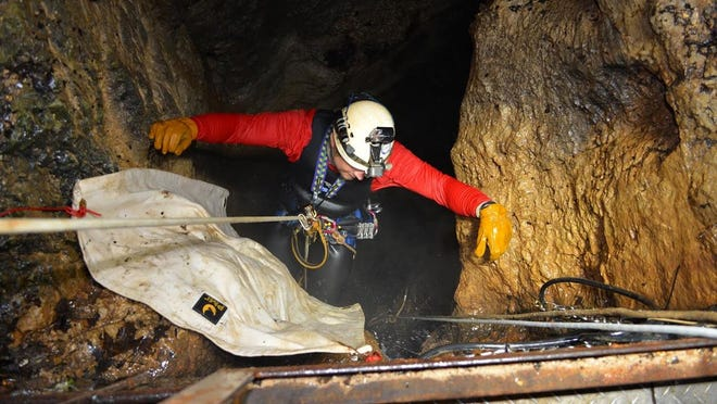 Cave Research Foundation team leader Tony Schmitt works his way up the line after spending nearly four hours exploring Devils Well.