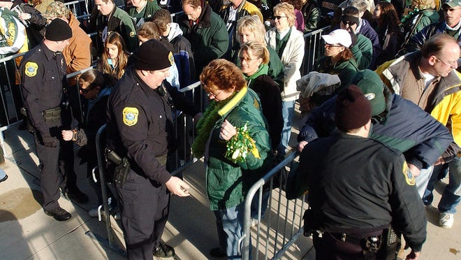 Green Bay Police Department officers check fans as they enter at the Oneida Gate of Lambeau Field in Green Bay.