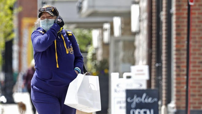 A woman adjusts her face mask while shopping along North High Street in the Short North last month. Some small business owners in central Ohio are worried that sales have not recovered to pre-pandemic levels, and that without further federal assistance, they'll have to reduce staff or close.
