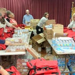 Staff and Auxiliary members at Gila Regional Medical Center assemble red bags for Healthy Senior Initiative grant-funded project. Left to right: Amanda Holguin, Howie Morales, Frances Day, Holley Hudgins, Marge Srack, Vera MacGregor, Charles Messberg, Lisa Munoz, Lil Christian, Joann Holguin