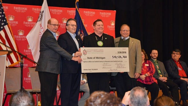 Jamie Stuck, Tribal Council chairman of the Nottawaseppi Huron Band of the Potawatomi, presents a check for $18,126,750 to State Sen. Michael Nofs, State Rep. John Bizon and State Rep. David Maturen.