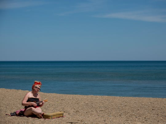 Alyssa Ferri, of Port Huron, sings and plays the ukulele on the beach Thursday, June 2, 2016 at Lakeside Park in Port Huron. The city is looking at ways to handle increasing crowds after nearly 7,000 people filled the park on Memorial Day.