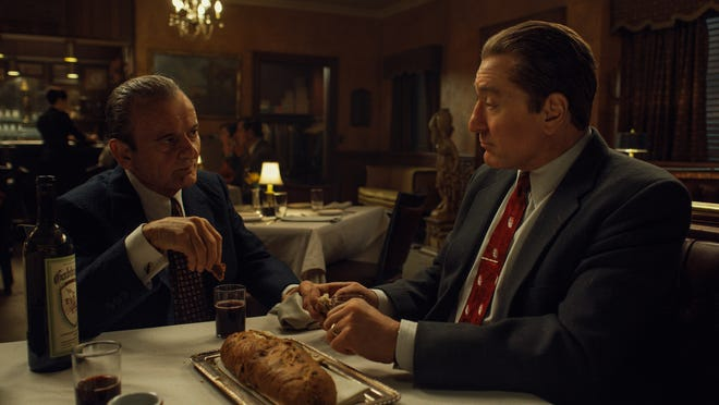 Dipping bread in wine, known as Intinction, speaks to the shared Catholic traditions of Russell Bufalino (Joe Pesci) and Frank Sheeran (Robert De Niro).