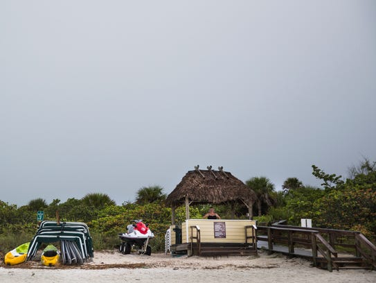 Beth Mardis stands under a shelter on Barefoot Beach