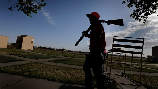 Caleb Najera of the Desert Valley 4-H Shooting Sports team walks with his shotgun to practice trap Saturday morning as his team prepares for the state competition.