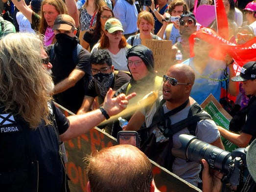 A white nationalist gives a counter protester the finger