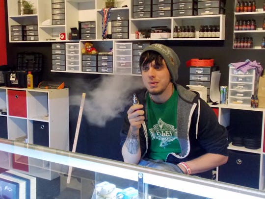 In this Jan. 13, 2015 photo, Tyler Newman, 24, vapes