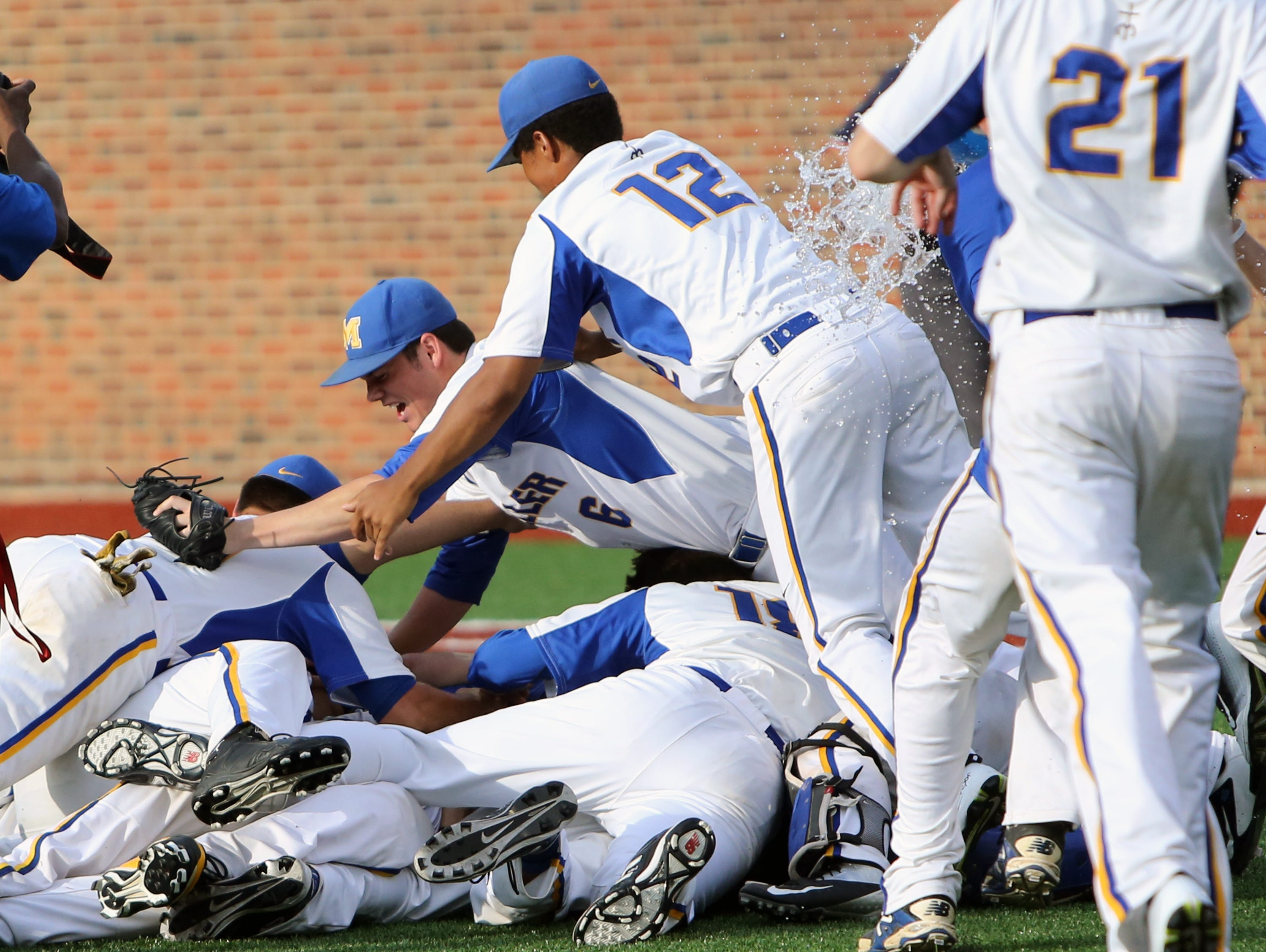 Moeller pitcher Joe Vranesic (6) manages to escape being mobbed by his teammates, then joins the celebration pile.