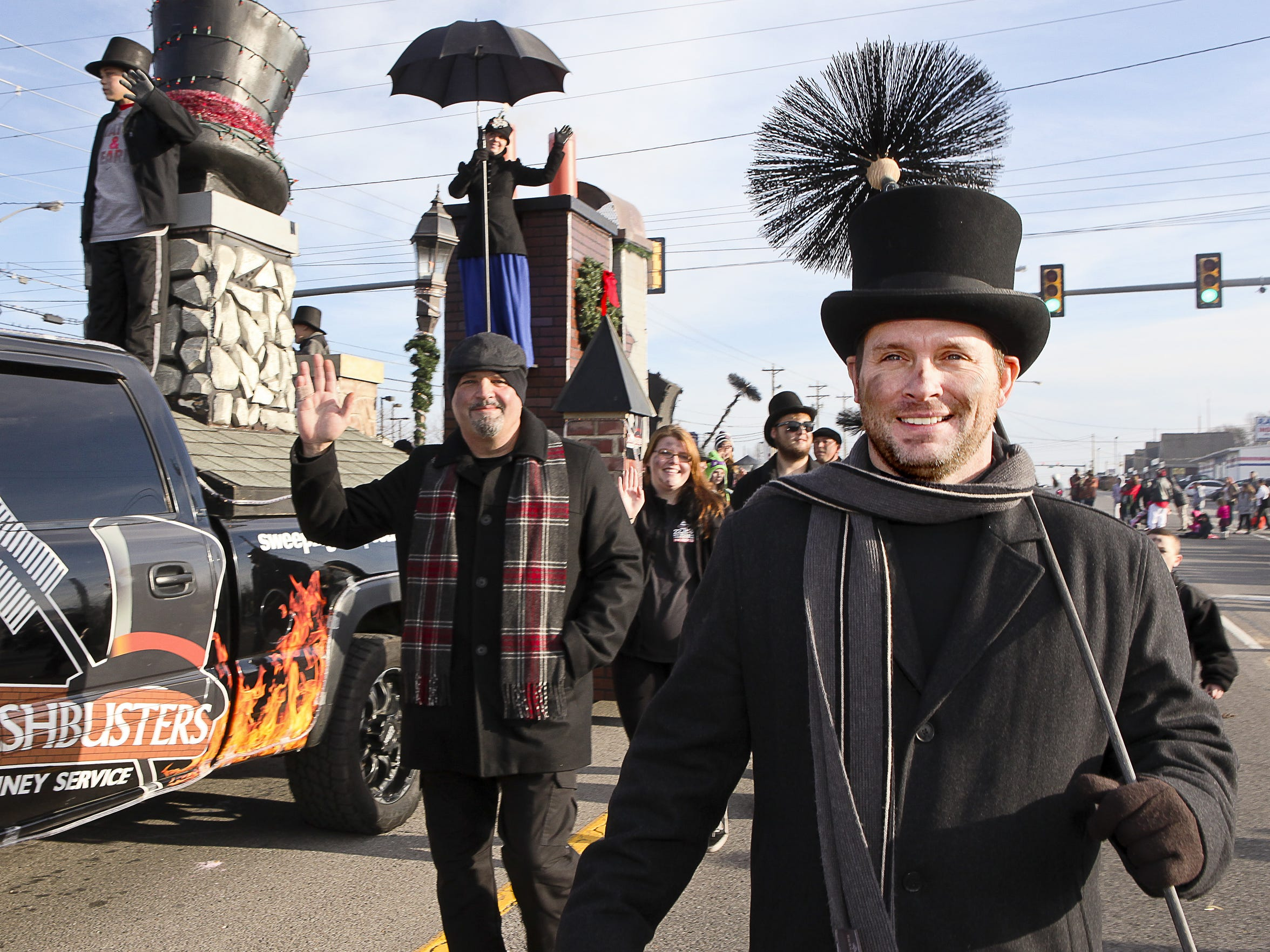 Chimney sweep Mark Stoner leads his fellow sweeps down Lowry Street beside a Mary Poppins-themed float in last year's Smyrna Christmas parade.