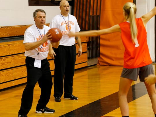 Marathon assistant coach Mick Lowie inbounds the ball as coach Andrew Pierce looks on during a recent practice.