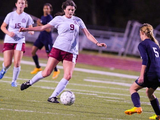 #9 Hailey Zaunbrecher drives the ball past a defender