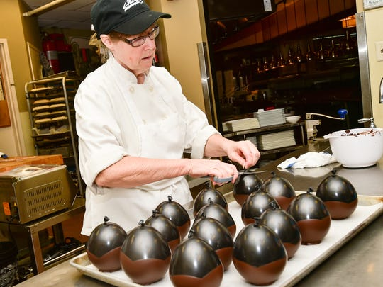 Sue Barras uses balloons to make edible chocolate cups for mousse Charley G's. She recently resumed her role as the restaurant's pastry chef after a few years away.