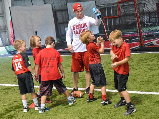 UL defensive Intern Joe Gallo helps campers cool off during the Cajuns' youth football camp last week.