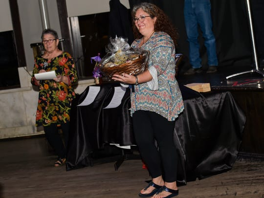 Specially decorated jars of St. Julien's Goods figs were part of a live auction Tuesday to raise money to establish an endowed chair at UL in John St. Julien's name. (Pictured- Layne St Julien (L) and Erin May)