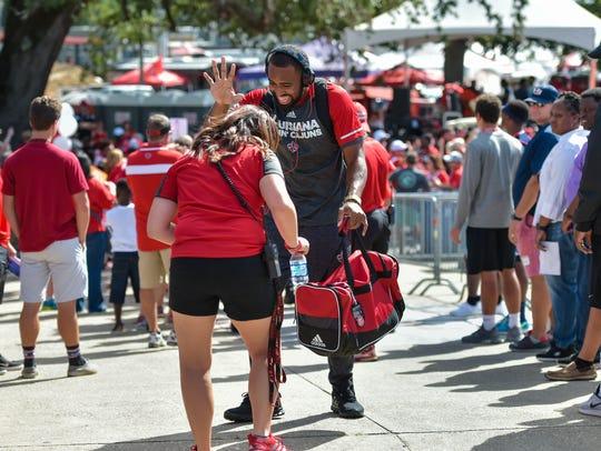 A fan stops UL quarterback Anthony Jennings for a good