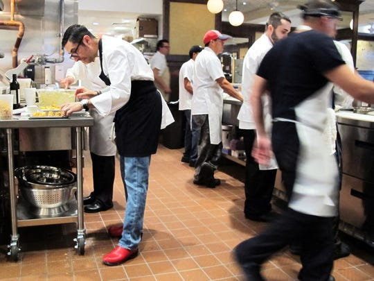 Chef-owner Vincenzo Betulia, left, prepares appetizers with his team in the kitchen at a pre-opening event at The French, 365 Fifth Ave. S., Naples.