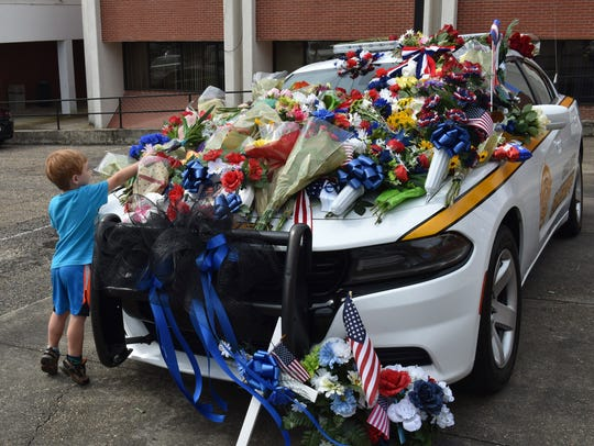 Shelton Hall places a flower on the car of Sheriff's